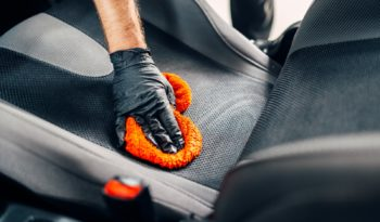 Professional chemical cleaning of car seats with spoonge. Carwash service, male worker in gloves using special agent