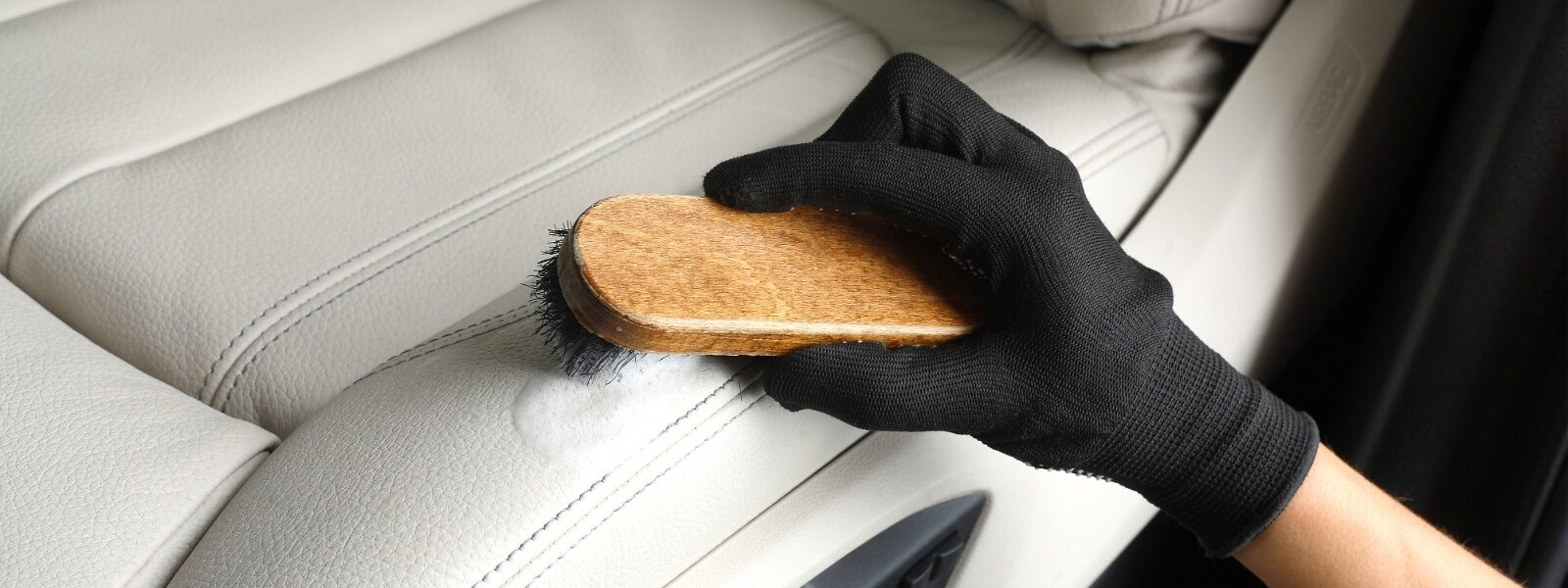 Worker washing of interior by a soft brush with foam.
