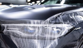 Car detailing specialist installing protective transparent foil on car body and lmp